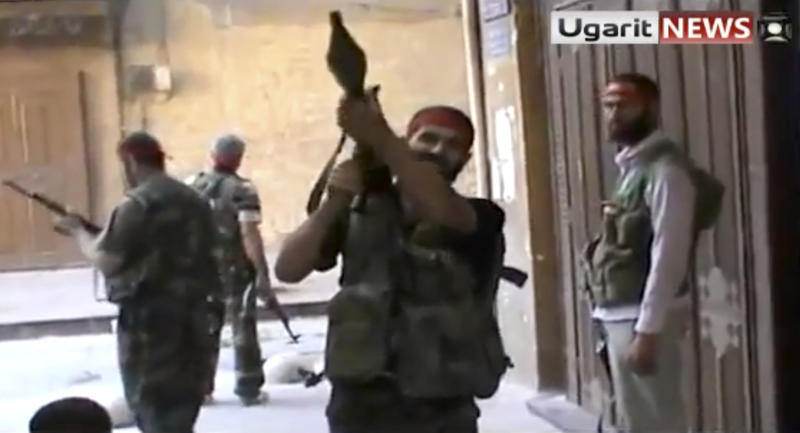 In this image taken from video obtained from Ugarit news, which has been authenticated based on its contents and other AP reporting, Syrian rebels gather as they engage government forces in Aleppo, Syria, Friday, Sept. 28,2012. Syrian rebels and residents of Aleppo struggled Saturday to contain a huge fire that destroyed parts of the city's medieval souks, or markets, following raging battles between government troops and opposition fighters there, activists said. Some described the overnight blaze as the worst blow yet to a historic district that helped make the heart of Aleppo, Syria's largest city and commercial hub, a UNESCO world heritage site. (AP Photo/Ugarit News via AP video)