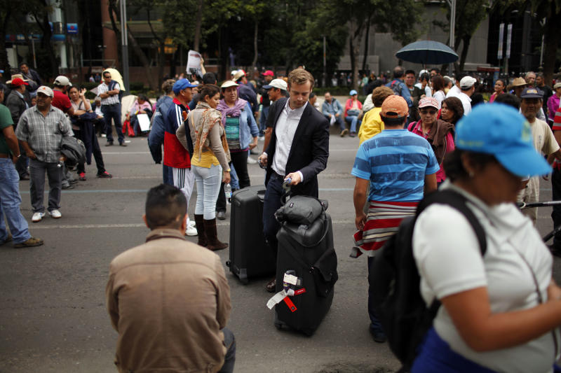 A man with rolling suitcases weaves his way through protesters toward a hotel on Paseo de la Reforma in Mexico City, Wednesday, Sept. 4, 2013. Striking teachers continued their protest against education reform after Mexico's Senate overwhelmingly passed the sweeping reform of Mexico's public school system early Wednesday, handing President Enrique Pena Nieto an important victory in his push to remake some of his country's institutions. (AP Photo/Ivan Pierre Aguirre)