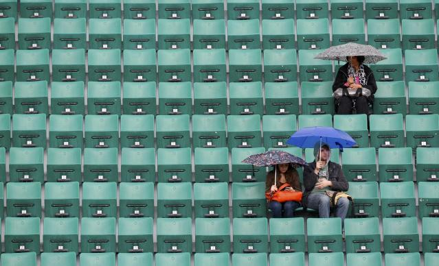 Spectators protect themselves from the rain with umbrellas before the start of the women's quarter-final match between Sara Errani of Italy and Andrea Petkovic of Germany during the French Open tennis tournament at the Roland Garros stadium in Paris June 4, 2014. REUTERS/Jean-Paul Pelissier (FRANCE - Tags: SPORT TENNIS ENVIRONMENT)