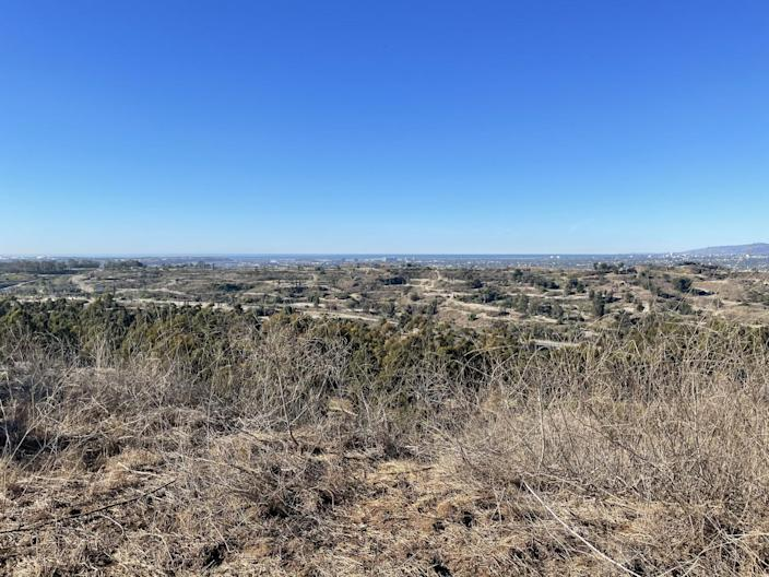 The view from Inspiration Point in Kenneth Hahn state park looks out on a dirt landscape dotted with oil pumps.