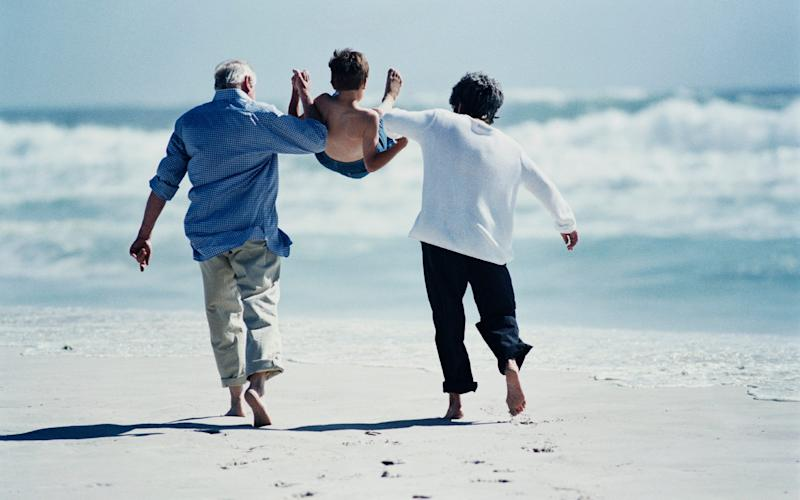 An elderly couple and their grandson - Credit: Getty/AgeUK say many families could not cope without the help of grandparents