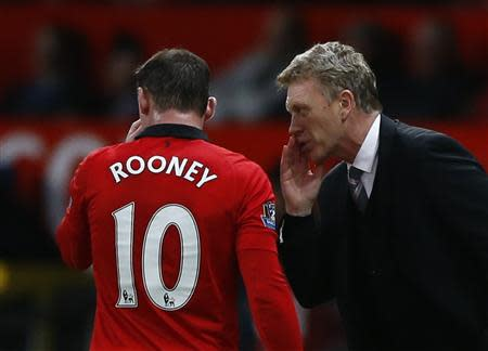 Manchester United's manager David Moyes (R) speaks to Wayne Rooney during their English Premier League soccer match against West Ham at Old Trafford in Manchester, northern England December 21, 2013. REUTERS/Darren Staples