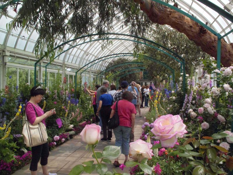 """In this May 26, 2012 photo, visitors to the New York Botanical Garden in New York walk through """"Monet's Garden,"""" which evokes the impressionist artist Claude Monet's garden at Giverny, his home in France, from 1883 until his death in 1926. The exhibit runs through Oct. 21. (AP Photo/Ray Stubblebine)"""