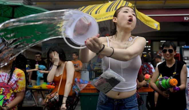 A Chinese tourist throws a bucket of water during celebrations for Songkran, also known as the Thai New Year in Bangkok. Photo: AFP