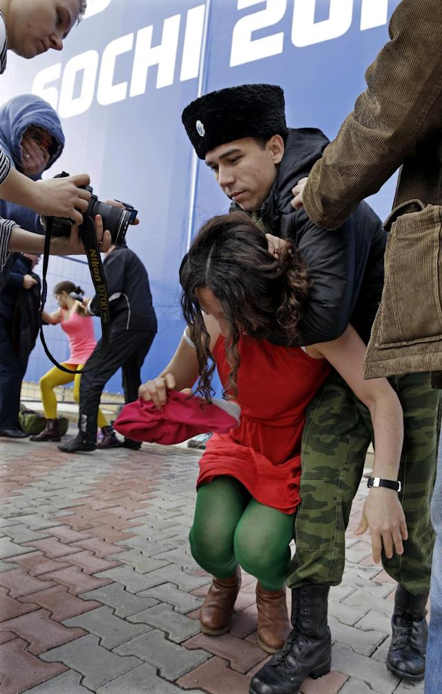 A member of the punk group Pussy Riot is restrained by a member of the Cossack militia in Sochi, Russia, on Wednesday, Feb. 19, 2014. Cossack militia attacked the Pussy Riot punk group with horsewhips on Wednesday as the group tried to perform under a sign advertising the Sochi Olympics. The group had gathered to perform in a downtown Sochi restaurant, about 30km (21miles) from where the Winter Olympics are being held.They left the restaurant wearing bright dresses and ski masks and had only been performing for a few seconds when they were set upon by Cossacks