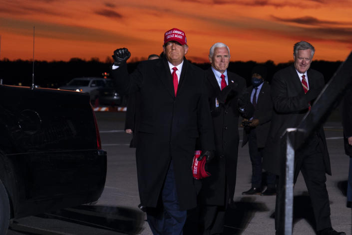 President Donald Trump and Vice President Mike Pence arrive for a campaign rally at Cherry Capital Airport, Monday, Nov. 2, 2020, in Traverse City, Mich. At right is White House chief of staff Mark Meadows. (AP Photo/Evan Vucci)