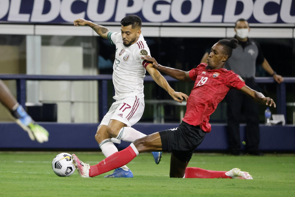 Mexico forward Jesus Corona (17) has the ball kicked away by Trinidad and Tobago defender Ross Russell (19) during the first half of a CONCACAF Gold Cup Group A soccer match in Arlington, Texas, Saturday, July 10, 2021. (AP Photo/Michael Ainsworth)