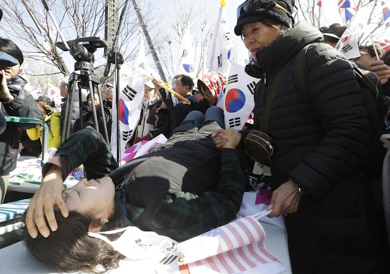 A fainted supporter of South Korean President Park Geun-hye lies on a table during a rally opposing her impeachment near Constitutional Court in Seoul, South Korea, Friday, March 10, 2017. In a historic ruling Friday, South Korea's Constitutional Court formally removed the impeached president from office over a corruption scandal that has plunged the country into political turmoil, worsened an already-serious national divide and led to calls for sweeping reforms. (AP Photo/Ahn Young-joon)
