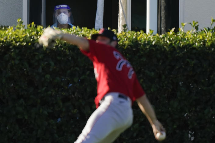 Boston Red Sox pitcher Jay Groome (77) throws the ball as a medical worker with a face shield near a testing site watches the players during spring training baseball practice on Monday, Feb. 22, 2021, in Fort Myers, Fla. (AP Photo/Brynn Anderson)