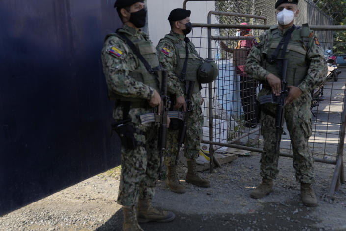 A resident looks through a gate surrounding the Litoral Penitentiary as security forces stand guard after deadly fights inside the jail in Guayaquil, Ecuador, Thursday, July 22, 2021. Rival gangs of inmates fought in two prisons in Ecuador, killing at least 18 people and injuring dozens, authorities said Thursday. (AP Photo/Dolores Ochoa)