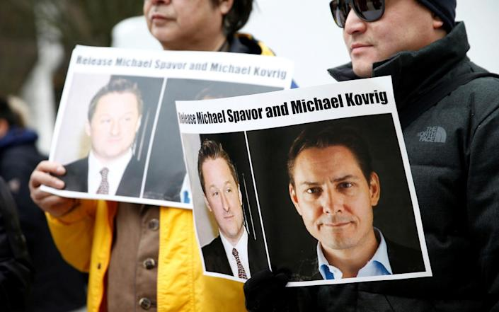 People hold signs calling for China to release Canadian detainees Spavor and Kovrig - REUTERS/Lindsey Wasson/File Photo