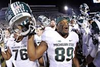 Michigan State defensive end Shilique Calhoun (89) joins his teammates in singing the Michigan State alma mater after a 34-10 win over Penn State in an NCAA college football game in State College, Pa., Saturday, Nov. 29, 2014. (AP Photo/Gene J. Puskar)