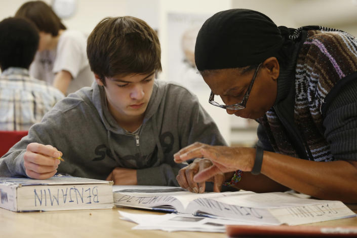 Student James Montalbano, 11th grade, works with teacher Angela Benjamin in the Advanced Placement (AP) Physics class at Woodrow Wilson High School in Washington, Friday, Feb. 7, 2014. The College Board says in a new report that the number of U.S. public students taking Advanced Placement classes doubled over the last decade. The class of 2013 of took 3.2 million AP exams. (AP Photo/Charles Dharapak)