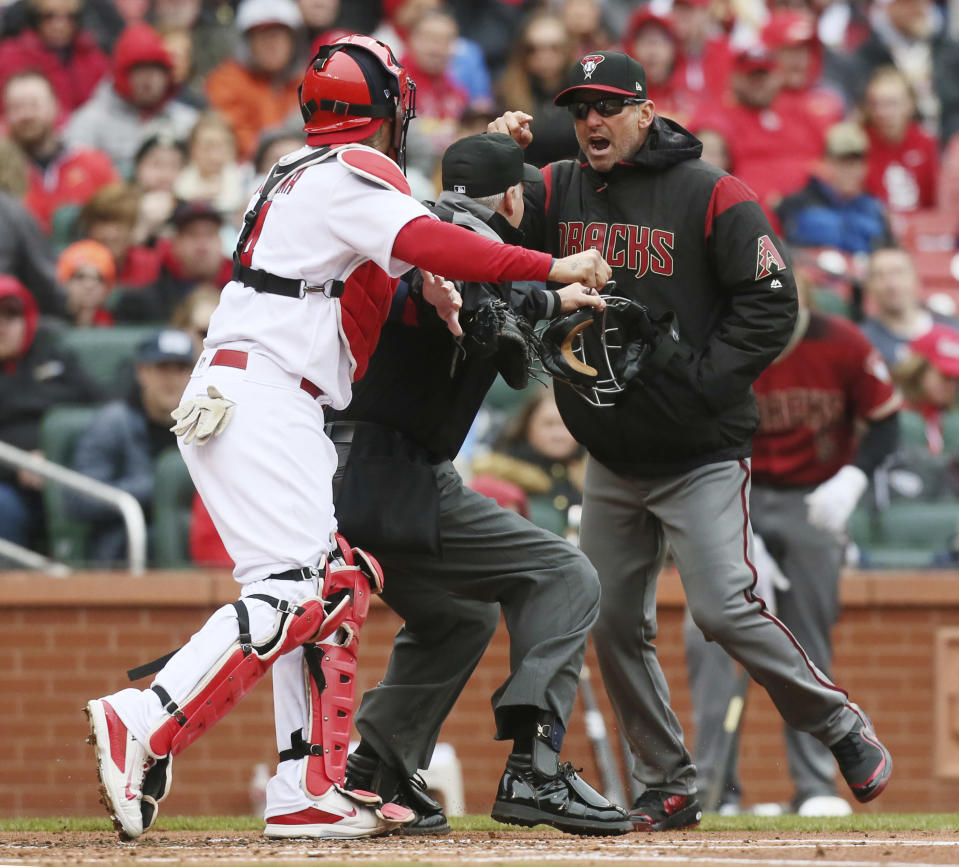 Arizona Diamondbacks manager Torey Lovullo gestures at St. Louis Cardinals catcher Yadier Molina as he argues balls and strikes with home plate umpire Tim Timmons in the second inning of a baseball game on Sunday, April 8, 2018, in St. Louis, Mo. Molina took offense to Lovullo's comments which led to a bench-clearing scuffle at home plate. (Chris Lee/St. Louis Post-Dispatch via AP)