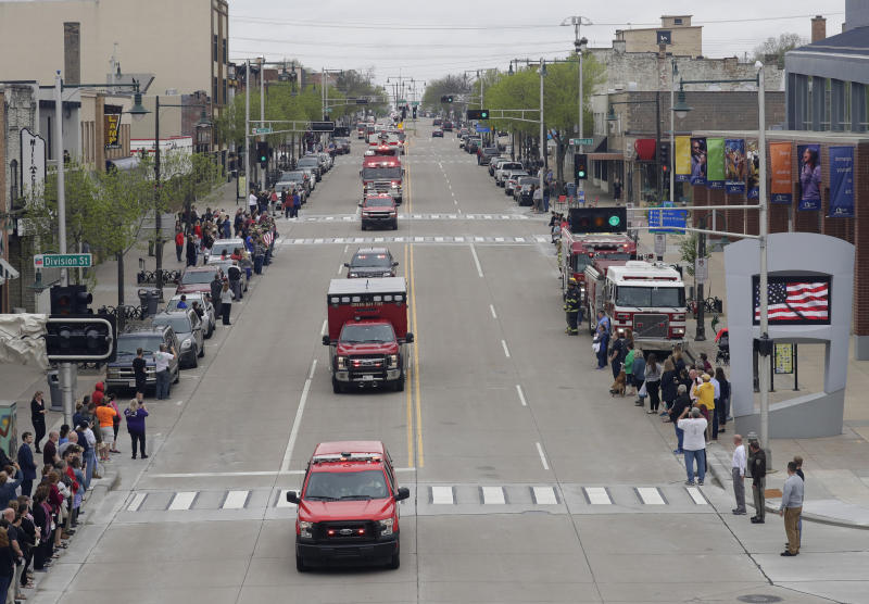 In this Thursday, May 16, 2019 photo, a procession for firefighter Mitch Lundgaard who was shot and killed while responding to a medical call at the Valley Transit Center moves along College Avenue in Appleton, Wis. (Dan Powers/The Post-Crescent via AP)