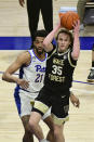 Wake Forest forward Carter Whitt drives past Pittsburgh forward Terrell Brown during the first half of an NCAA college basketball game, Tuesday, March 2, 2021, in Pittsburgh. (AP Photo/Fred Vuich)