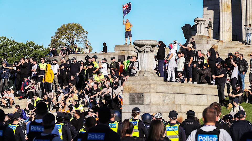 A man, pictured here waving the Australian flag on the steps of the Shrine of Remembrance.