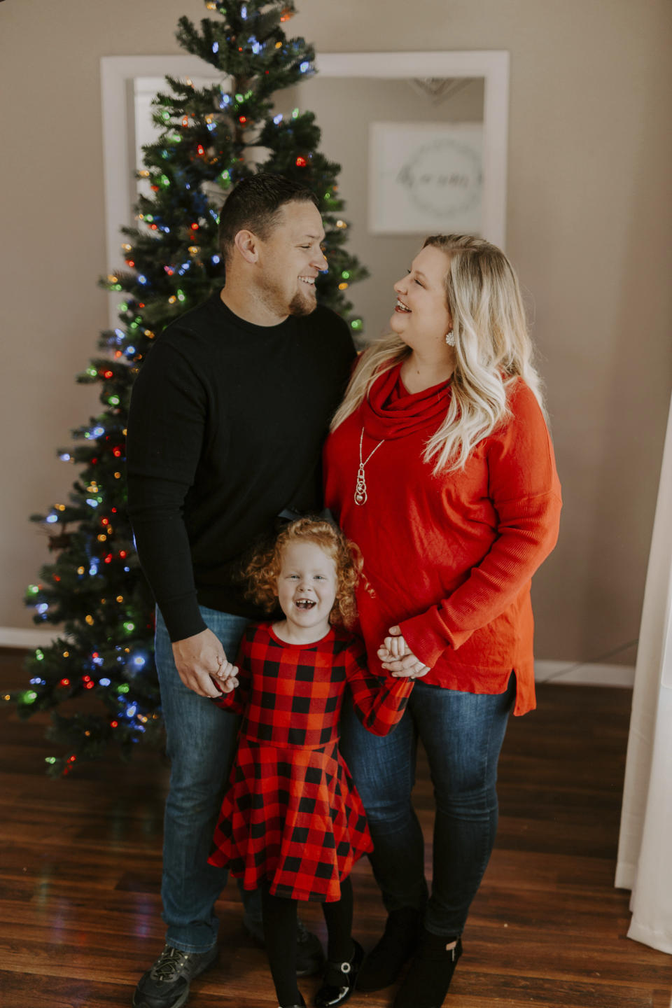 Nick Jones, left, poses with his wife Mindy Jones and their daughter Gracelyn Jones in front of one of their decorated Christmas trees at their home in Louisville, Ky. The Jones family are among a growing number of people who have gone full-on Christmas weeks early. Usually Mindy waits until the Saturday after Thanksgiving to jump start the holiday. (Jade Ware via AP)