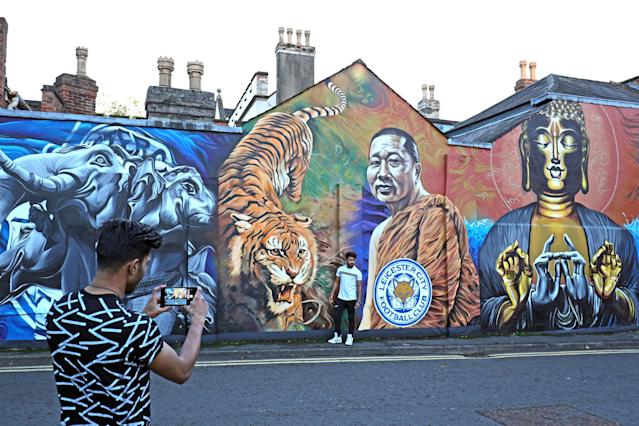 <p>A man takes a picture of his friend standing next to a mural of the Leicester City owner Vichai Srivaddhanaprabha. Aaron Chown/PA Wire </p>