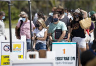 FILE - In this May 2, 2021, file photo, people line up to receive a Johnson & Johnson vaccine at the one-time pop-up vaccination site located 16th Street beach on the sand in Miami Beach. Nearly 45% of the nation's adults are fully vaccinated, and over 58% have received at least one dose, according to the Centers for Disease Control and Prevention. (David Santiago/Miami Herald via AP, File)