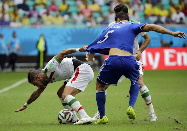 Iran's Ashkan Dejagah, left, pulls the shirt of Bosnia's Sead Kolasinac during the group F World Cup soccer match between Bosnia and Iran at the Arena Fonte Nova in Salvador, Brazil, Wednesday, June 25, 2014. (AP Photo/Sergei Grits)