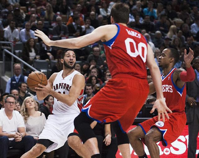 Toronto Raptors' Greivis Vasquez, left, looks to pass against Philadelphia 76ers' Spencer Hawes and Lorenzo Brown, right, during the first half of an NBA basketball game in Toronto on Friday, Dec. 13, 2013. (AP Photo/The Canadian Press, Aaron Vincent Elkaim)