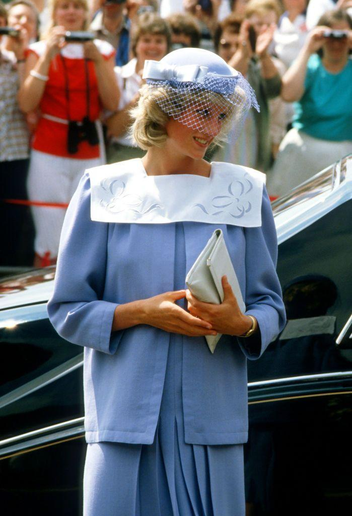 <p>The Princess of Wales wearing a blue maternity suit with a white square collar designed by Jan Van Velden and a John Boyd hat while on a visit to a hospital on June 27, 1984.</p>