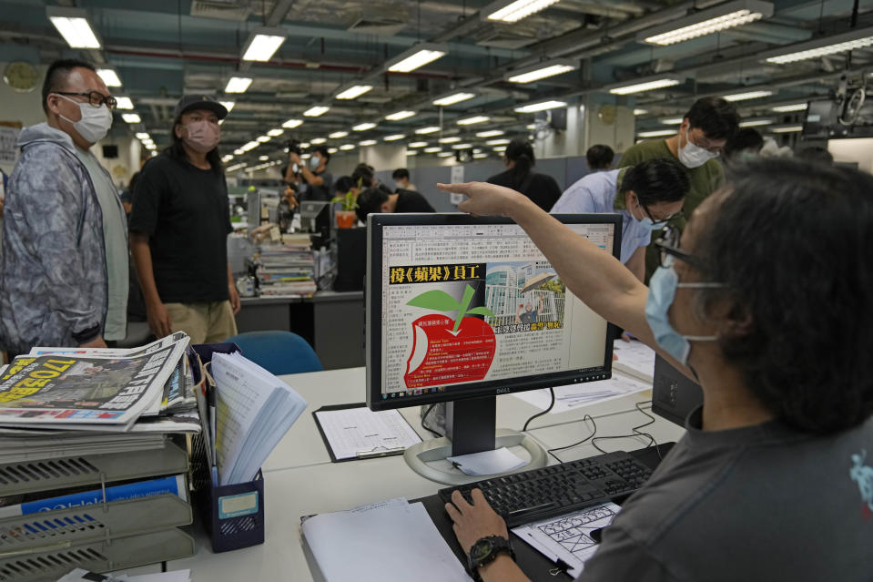 Workers design the layout of Apple Daily newspaper at the printing house in Hong Kong, early Friday, June 18, 2021. Five editors and executives at pro-democracy Apple Daily newspaper were arrested Thursday under Hong Kong's national security law, its stock was halted and police were searching its offices in moves raising concerns about the media's future in the city. (AP Photo/Kin Cheung)