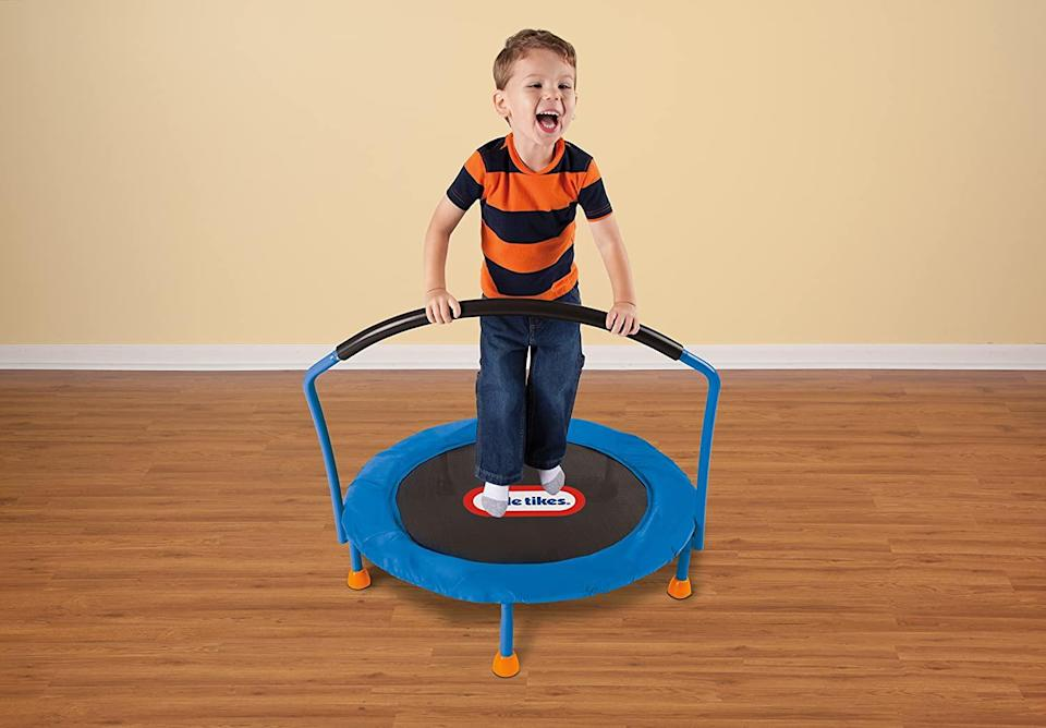 A child stands on a fisher price mini trampoline.