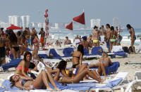 FILE - In this March 10, 2012 file photo, people fill the beach during Spring Break in Cancun, Mexico. Almost 7 million international tourists visit this stretch of coast every year, many of whom arrive at the Cancun airport and are bused or drive down the Riviera Maya. (AP Photo/Israel Leal, File)