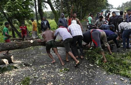 Men try to remove fallen trees from a road due to the rain and wind in Odisha October 12, 2013. REUTERS/Ahmad Masood