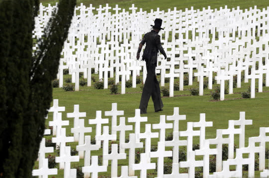 <p>A performer depicting death walks among tombstones at the French National Cemetery outside the Douaumont Necropolis and Ossuary, France, May 29, 2016, during a ceremony marking the 100th anniversary of the battle of Verdun, one of the largest battles of the First World War on the Western Front. <em>(Reuters/Philippe Wojazer)</em> </p>