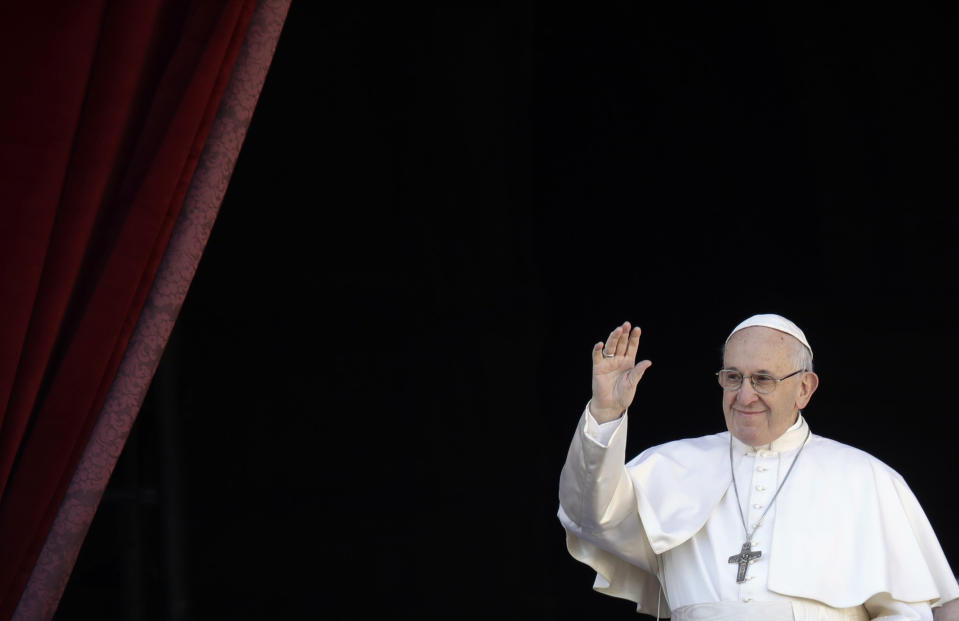 Pope Francis waves as he arrives to deliver the Urbi et Orbi (Latin for 'to the city and to the world' ) Christmas' day blessing from the main balcony of St. Peter's Basilica at the Vatican, Tuesday, Dec. 25, 2018. (AP Photo/Alessandra Tarantino)