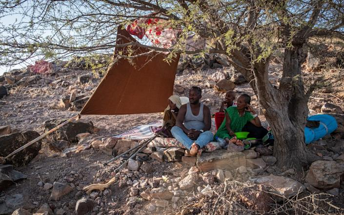 A family sits under a thorny acacia tree on one of the rolling hills that surround Um-Rakoba, a refugee camp that was built to host refugees fleeing the marxist Derg regime in 1985 - Joost Bastmeijer