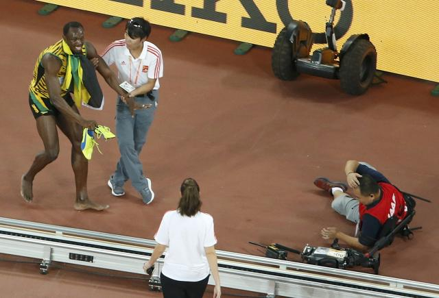 Winner Bolt of Jamaica gets up after being hit by a cameraman on a Segway after competing at the men's 200 metres final during the 15th IAAF World Championships at the National Stadium in Beijing