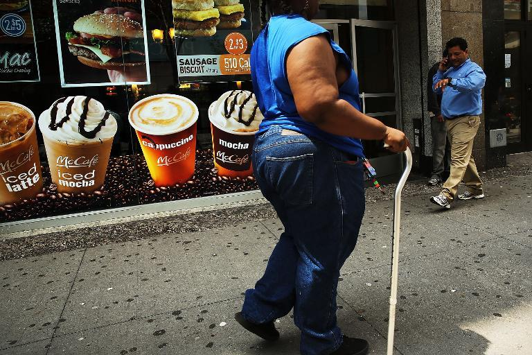 An obese woman walks in a Brooklyn neighborhood on June 11, 2013 in New York City
