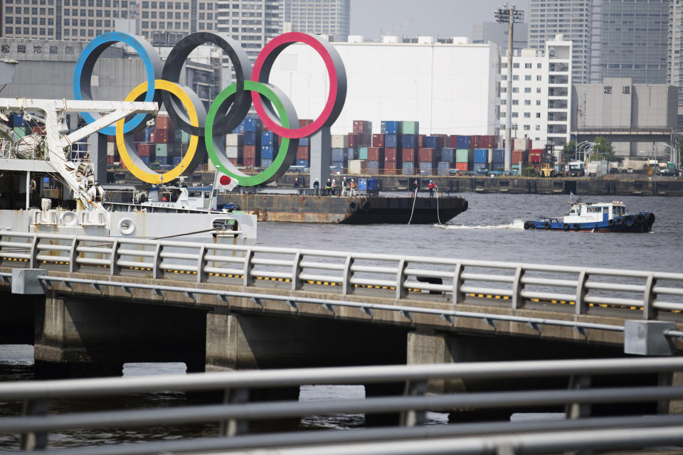 """Tugboats move a symbol installed for the Olympic and Paralympic Games Tokyo 2020 on a barge from its usual spot off the Odaiba Marine Park in Tokyo Thursday, Aug. 6, 2020. The five Olympic rings floating on a barge in Tokyo Bay were removed on Thursday for what is being called """"maintenance,"""" and officials says they will return to greet next year's Games. The Tokyo Olympics have been postponed for a year because of the coronavirus pandemic and are to open on July 23, 2021. The Paralympics follow on Aug. 24. (AP Photo/Hiro Komae)"""
