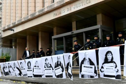 French police stand outside a court in the southeastern town of Gap where protesters have strung up signs backing three people on trial for helping migrants cross the Alps into France