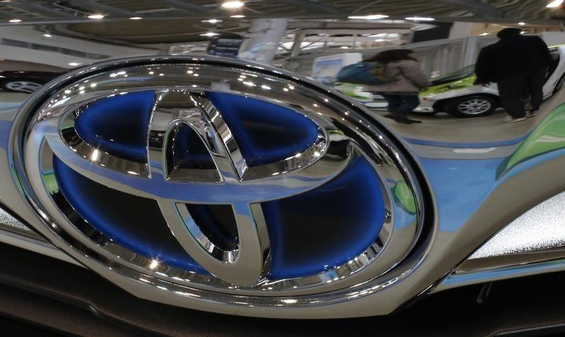 A visitor walking past cars is reflected on a Toyota car at the company's showroom in Tokyo