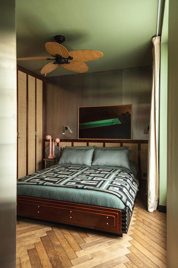 In the bedroom, painted in Lichen green by Farrow & Ball, Hugo Toro designed the bed. The Alualéatoure chair by Hélène de Saint Lager is used as a nightstand with a pink ceramic lamp by Entler Studio. The photo is by Clément Jolin, the curtains are by Silva Créations, and the bedding is by Society Limonta.