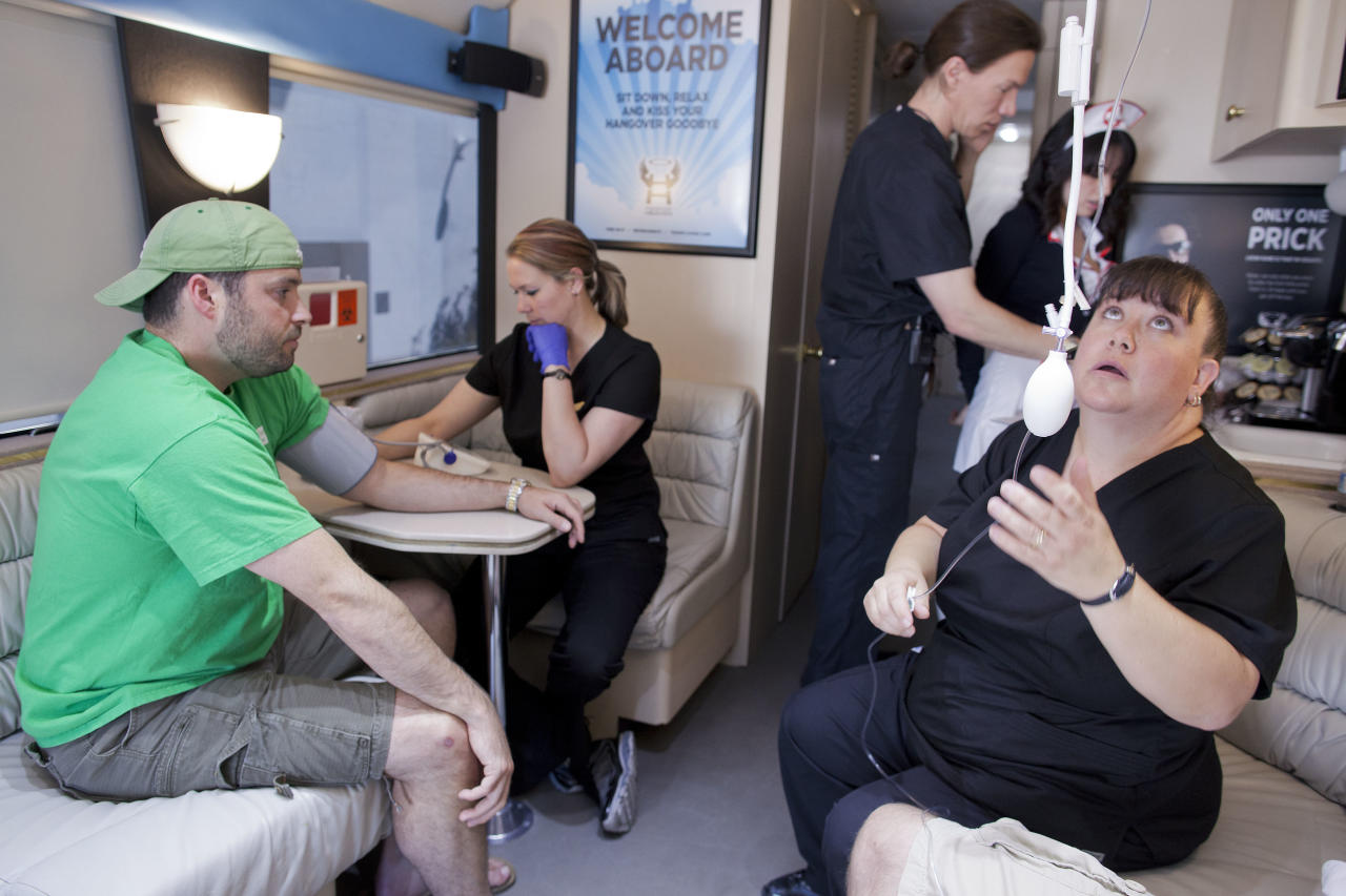 Emergency Medical Technician Debra Lund, right, checks the flow of an IV bag as EMT Stacey Kreitlow, second from left, takes the blood pressure of a patient and Dr. Jason Burke, third from left, and nurses assistant Crystal Willis look over his medical history while on Burke's Hangover Heaven bus, Sunday, April 15, 2012, in Las Vegas. Burke treated 16 patients on the first day of his mobile treatment center for tourists who spent the night before drinking in all the nightlife Las Vegas has to offer. For a fee, they get a quick morning-after way to rehydrate, rejuvenate and resume their revelry. (AP Photo/Julie Jacobson)