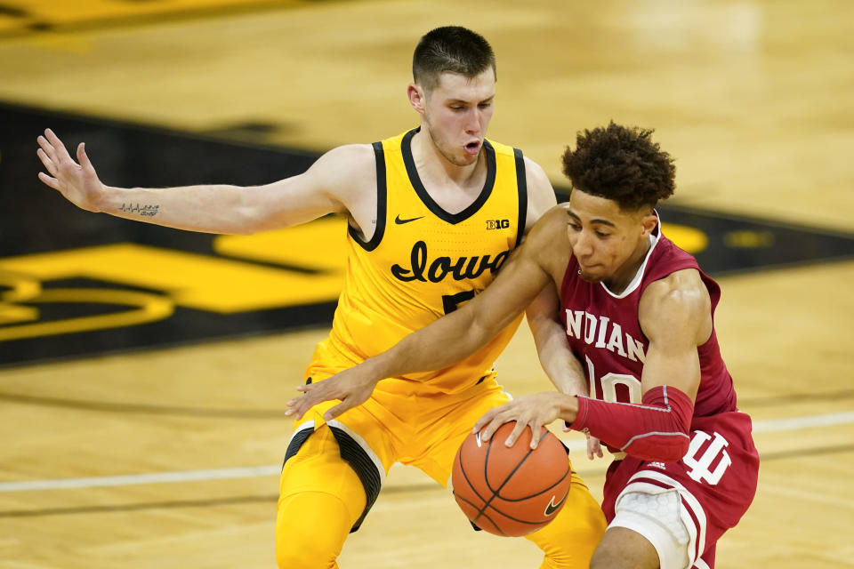 Iowa guard CJ Fredrick, left, tries to steal the ball from Indiana guard Rob Phinisee during the first half of an NCAA college basketball game, Thursday, Jan. 21, 2021, in Iowa City, Iowa. (AP Photo/Charlie Neibergall)