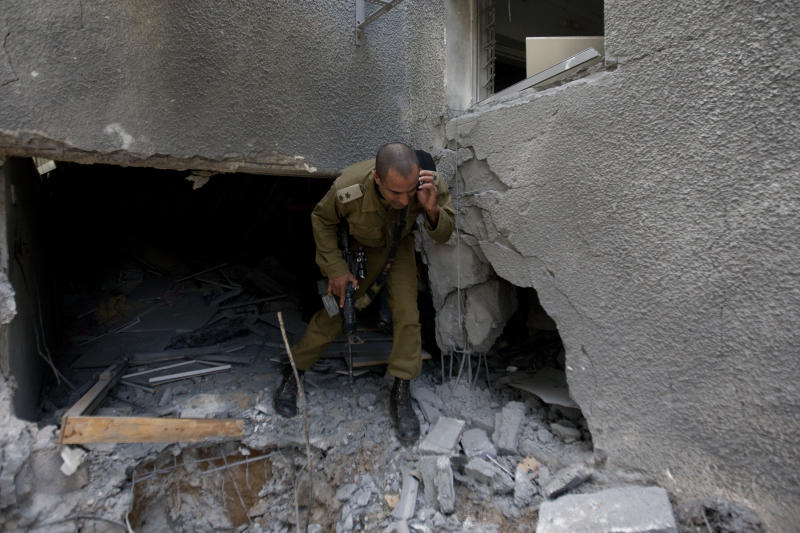 An Israeli military officer surveys the damage of house after a rocket fired by Palestinian militants hit a community along the Israel-Gaza Border, southern Israel, Wednesday, Oct. 24, 2012. Rockets and mortars from Gaza have pummeled southern Israel, drawing Israeli airstrikes that killed a Palestinian militant. The Israeli military said 60 rockets and mortars were fired by early morning Wednesday, following a volley the night before and that Israeli aircraft struck Gaza three times. (AP Photo/Ariel Schalit)