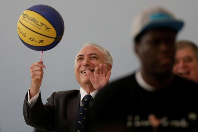 Brazil's President Michel Temer tries to control a basketball during a ceremony to announce the decree regulating the National Youth System (Sinajuve), at the Planalto Palace in Brasilia, Brazil March 15, 2018. REUTERS/Ueslei Marcelino