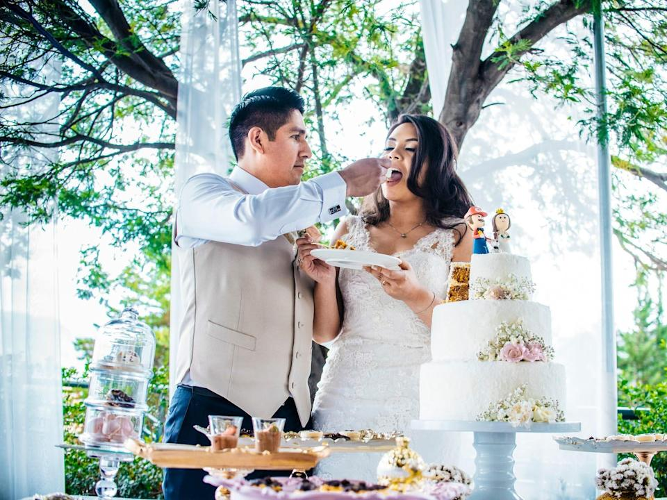 """A groom feeds a bride a bit of cake in front of trees. Their cake with a """"Mario""""-themed topper sits on a table in front of them."""