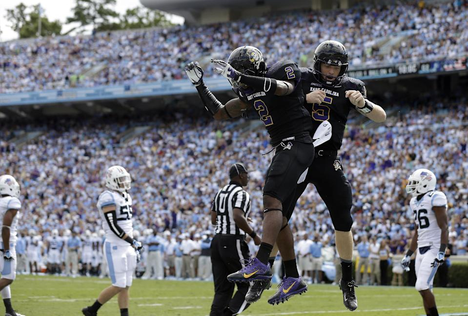 East Carolina quarterback Shane Carden (5) and Justin Hardy (2) celebrate Carden's touchdown against North Carolina during the first half of an NCAA college football game in Chapel Hill, N.C., Saturday, Sept. 28, 2013. (AP Photo/Gerry Broome)