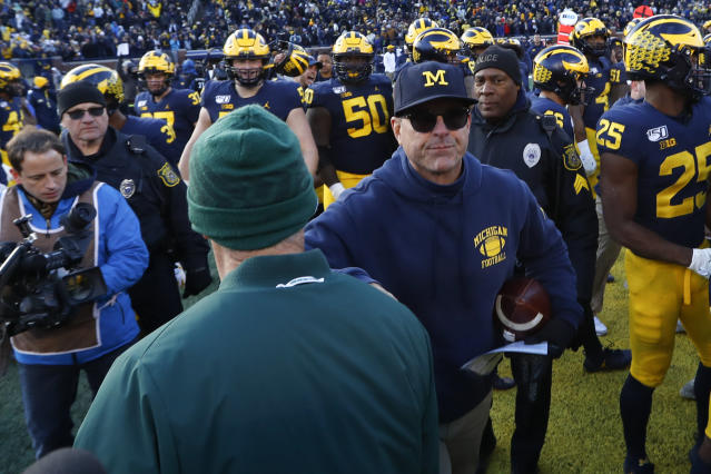 Michigan head coach Jim Harbaugh, right, and Michigan State head coach Mark Dantonio, back to camera, meet after an NCAA college football game in Ann Arbor, Mich., Saturday, Nov. 16, 2019. (AP Photo/Paul Sancya)