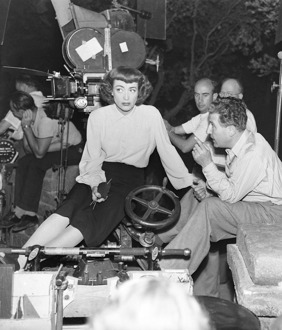 """<p>While on set for <em>Possessed, </em>Joan Crawford listens to notes from director Curtis Bernhardt. A clear sign the actress is in-between takes? The knitting needles in her hand, <a href=""""http://historyknits.blogspot.com/2013/03/famous-knitters-joan-crawford.html"""" rel=""""nofollow noopener"""" target=""""_blank"""" data-ylk=""""slk:a hobby she enjoyed"""" class=""""link rapid-noclick-resp"""">a hobby she enjoyed </a>whenever she had free time on set. </p>"""