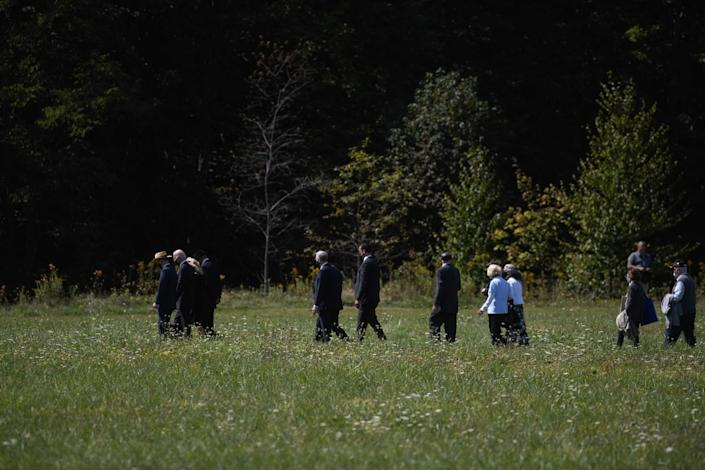 Several people in suits and dresses walk across a grassy field.