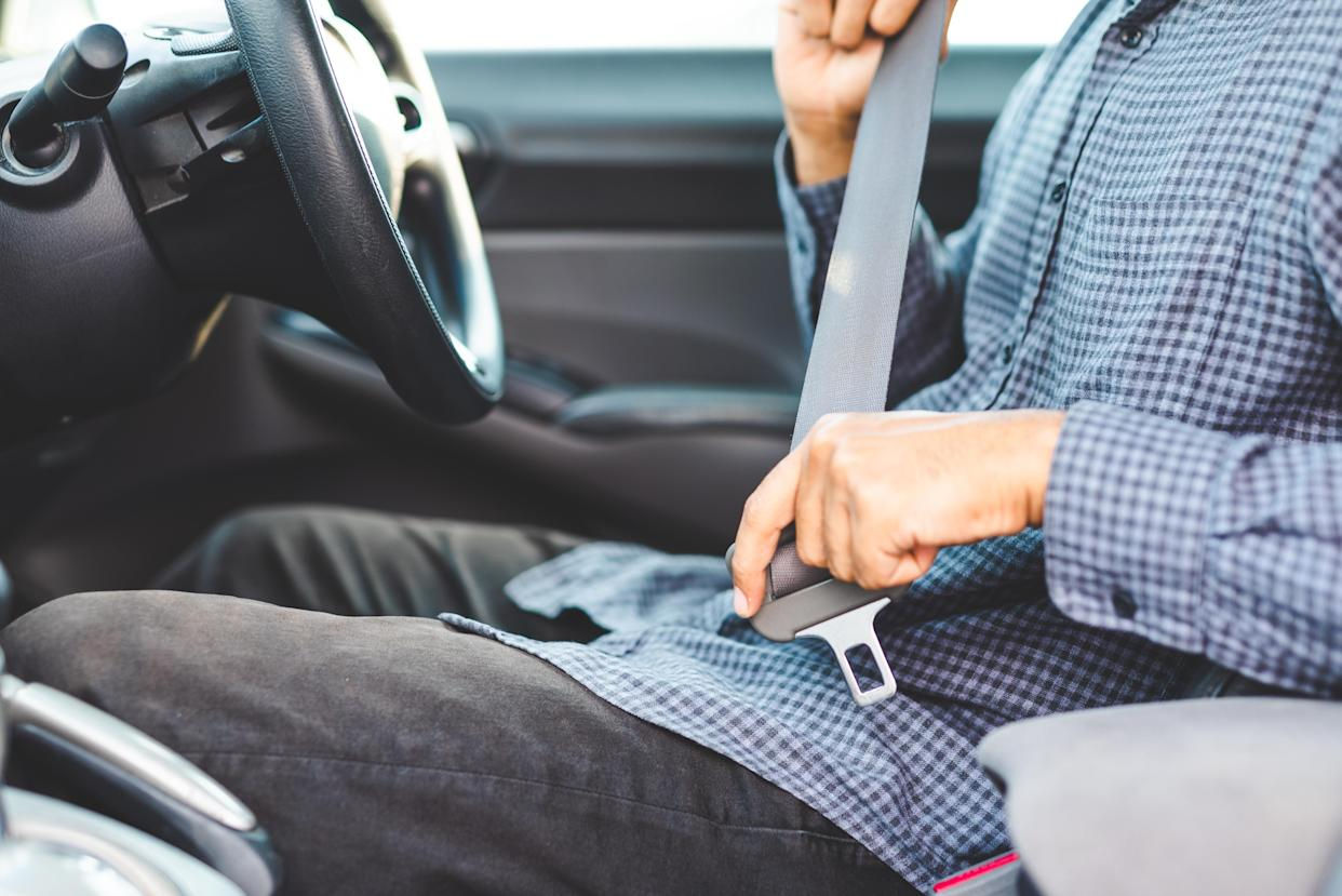 Close up hands man sitting on car seat and fastening seat belt, car safety concept.